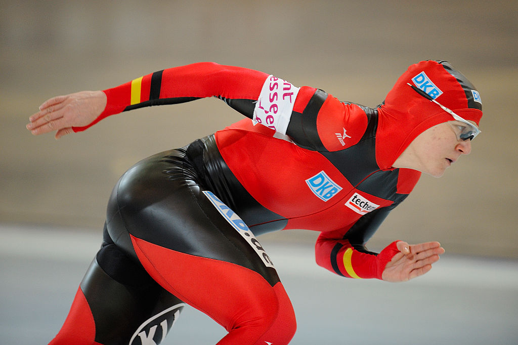 An athlete bends down to speed skate.