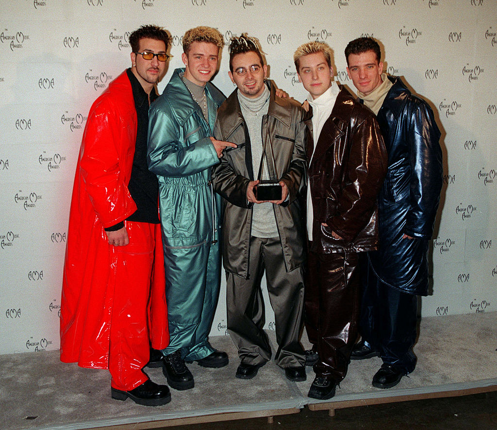 The group NSYNC poses together while holding an AMA award.
