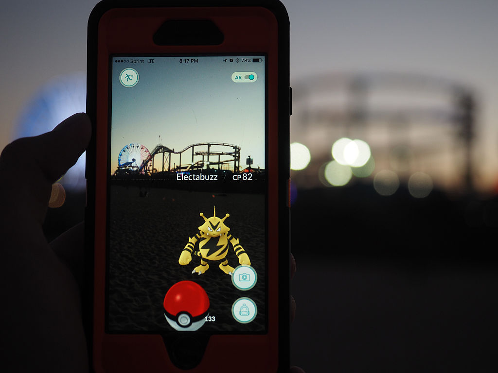 Someone hold up their smartphone to show Pokemon Go.