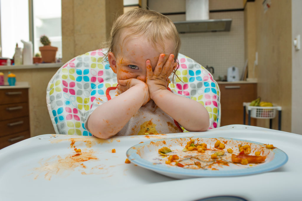A baby rubs sauce all over their face at their highchair.