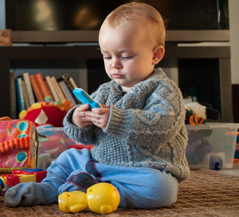 A baby boy plays with his toys in the living room.