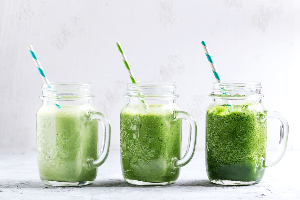 A green drink with a mason jar and straw is pictured.