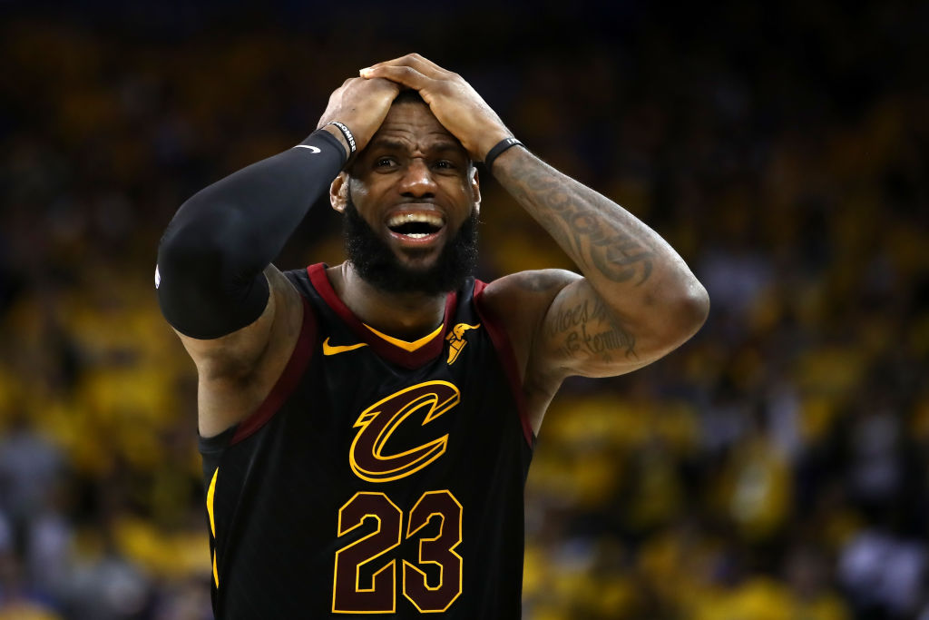 LeBron James puts his hands to his head and looks upset during a basketball game.