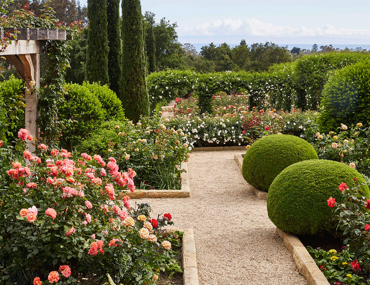 Oprah's garden features hedge arches, flowers, and wooden arches.