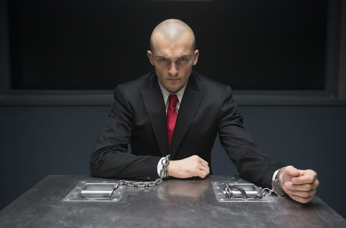 The lead of Agent 47 is cuffed and interviewed.