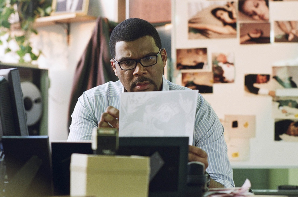 Tyler Perry reads a document while portraying Alex Cross.