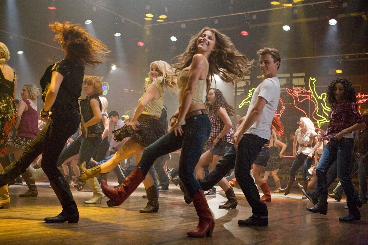 Performers line dance while shooting the movie Footloose.