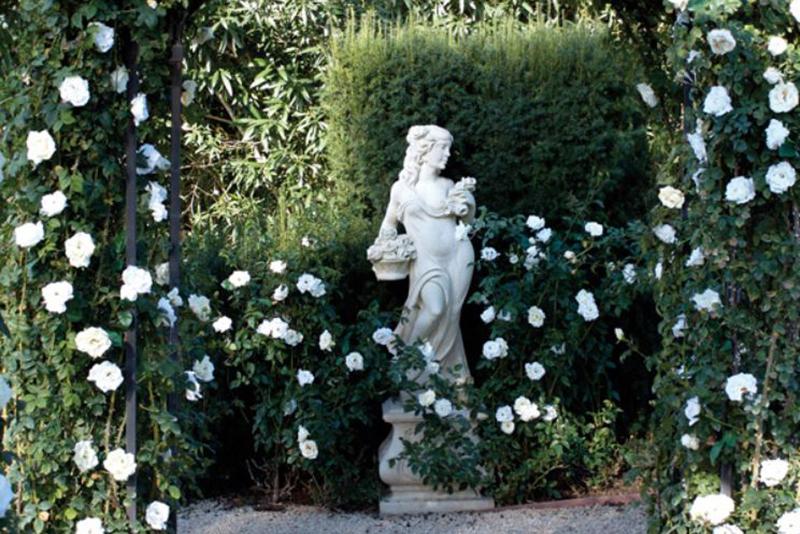 A statue and hydrangeas line hallelujah lane in Oprah's garden.