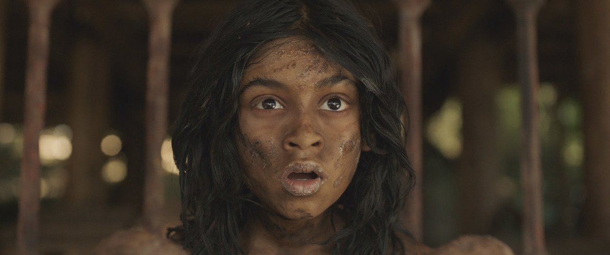 A closeup shows Mowgli covered in dirt and looking shocked.