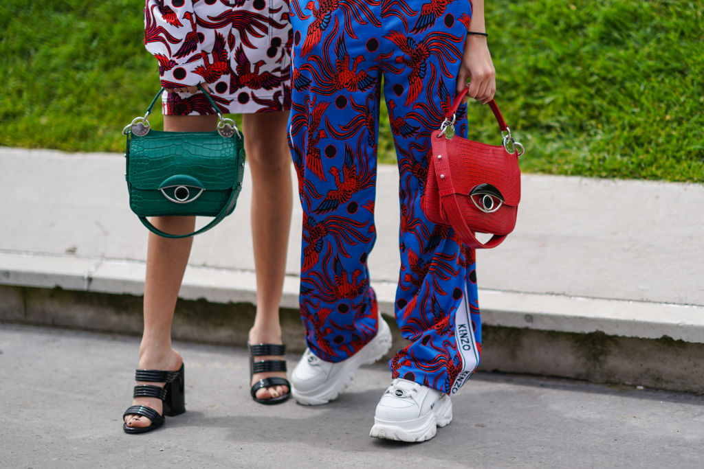 A guest (L) wears a white skirt with red birds design, a green Kenzo bag, black strappy sandals ; A guest (R) wears Kenzo blue pants with red birds design, a red Kenzo bag, white platform sneakers