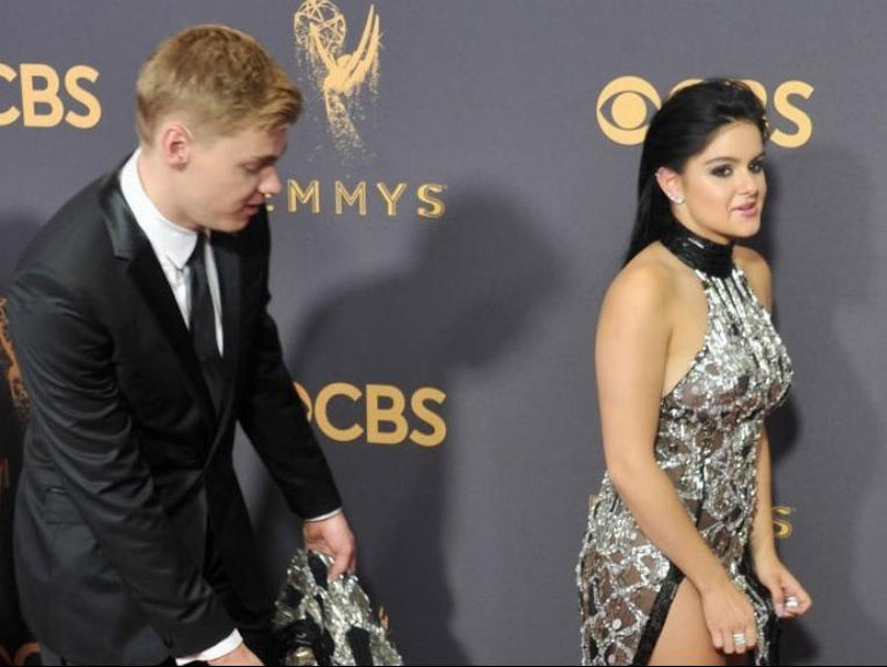 Levi Meaden helps Ariel Winter with the trail of her black and silver glistening gown.