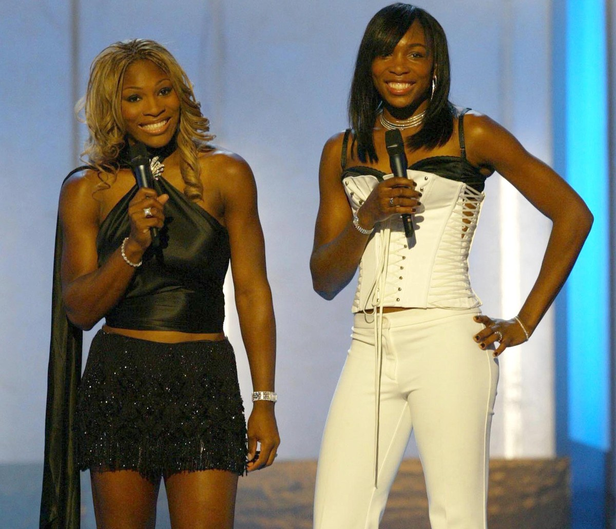 Serena and Venus Williams stand on stage during the 2002 VH1 Vogue Fashion Awards.