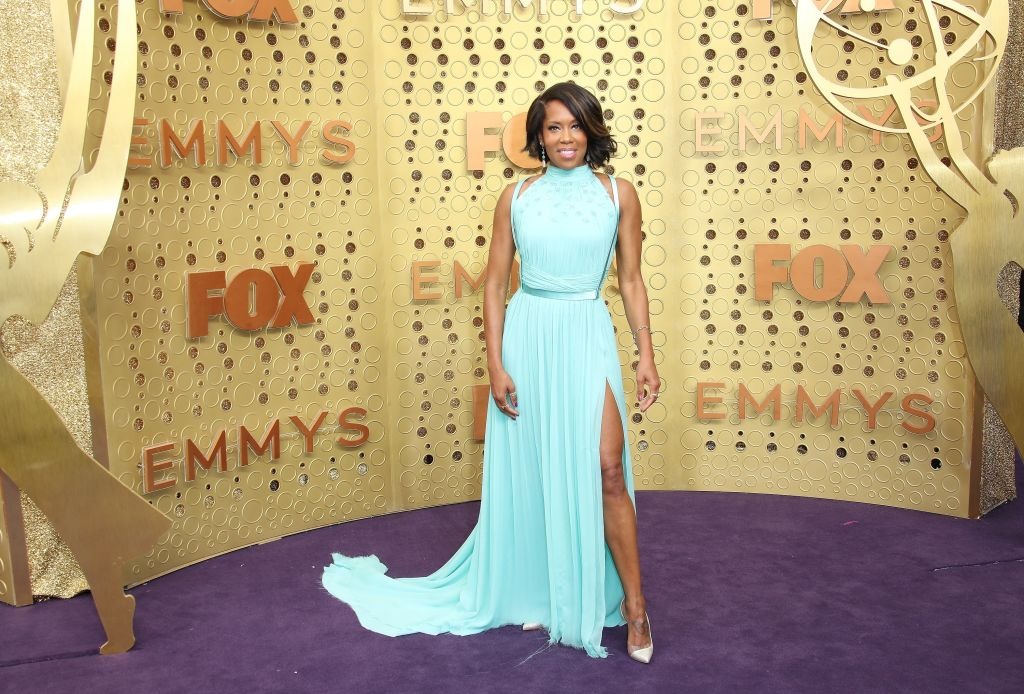 Regina King wears a long and flowy light-teal gown with a leg slit.