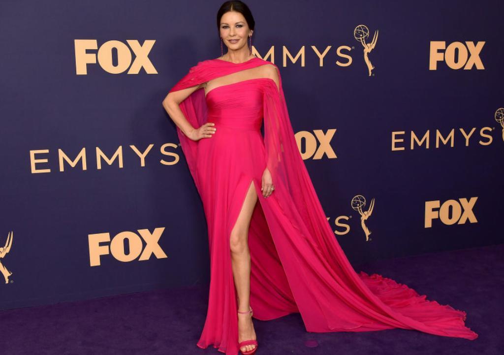 Catherine Zeta-Jones wears a long, hot-pink gown.