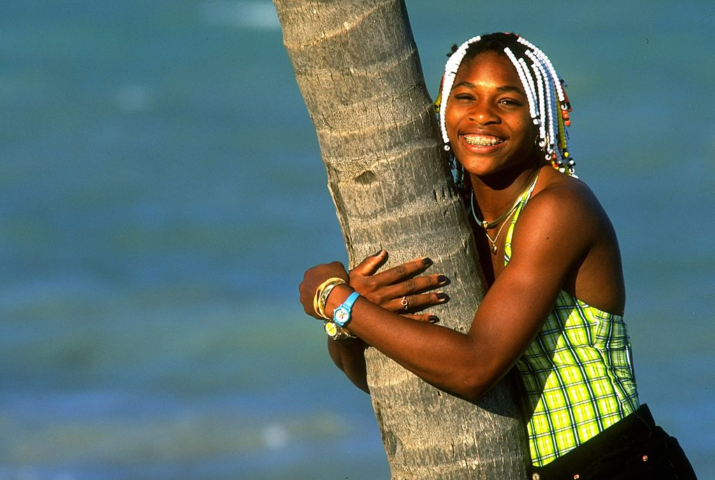 Teenage Serena Williams hugs a palm tree and smiles at the camera.