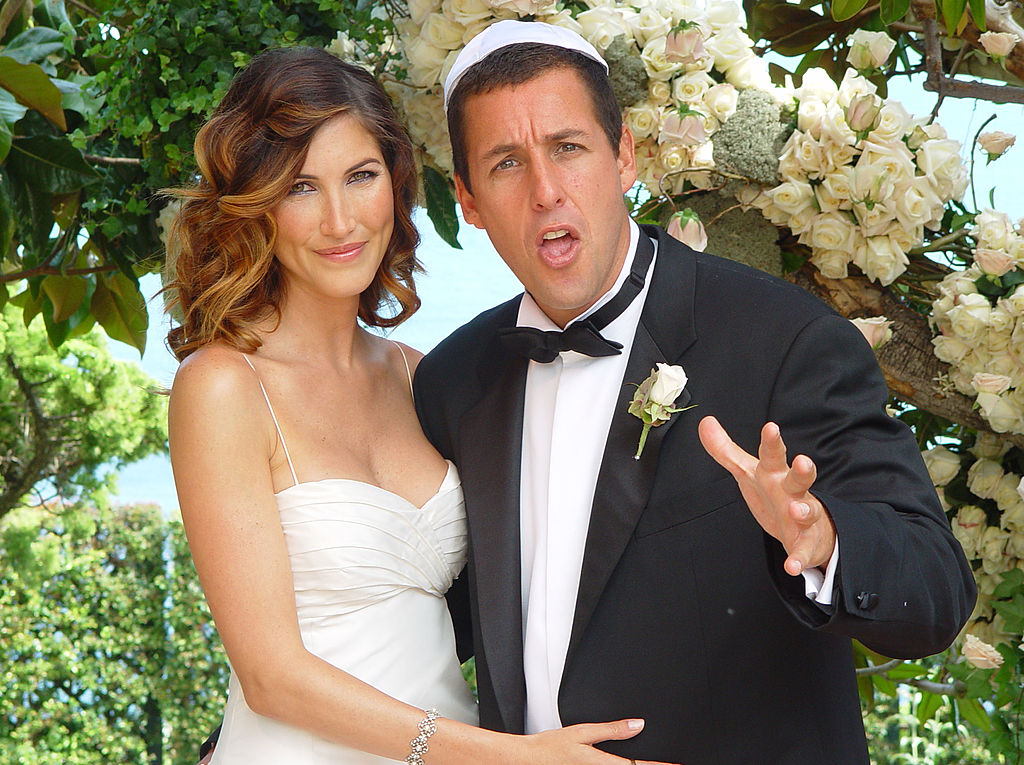 Adam Sandler wears a silly face while posing with his wife at their wedding.