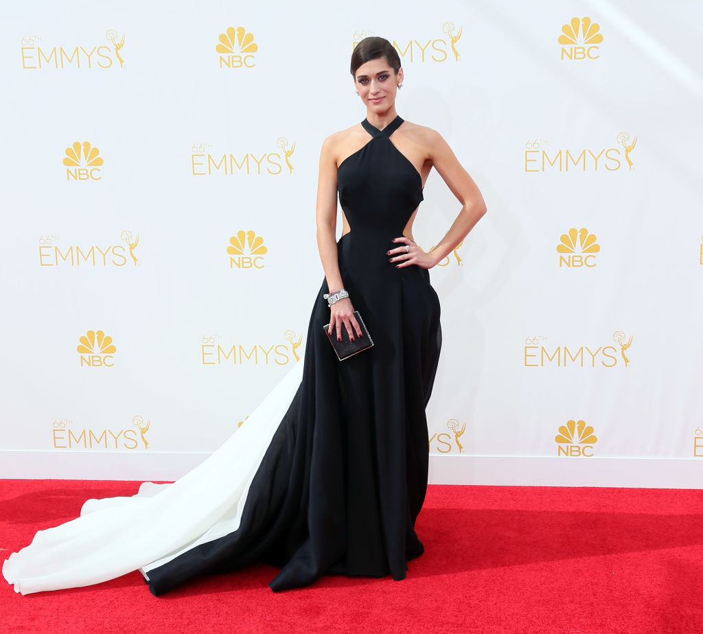 Lizzy Caplan wears a black gown with a white train.