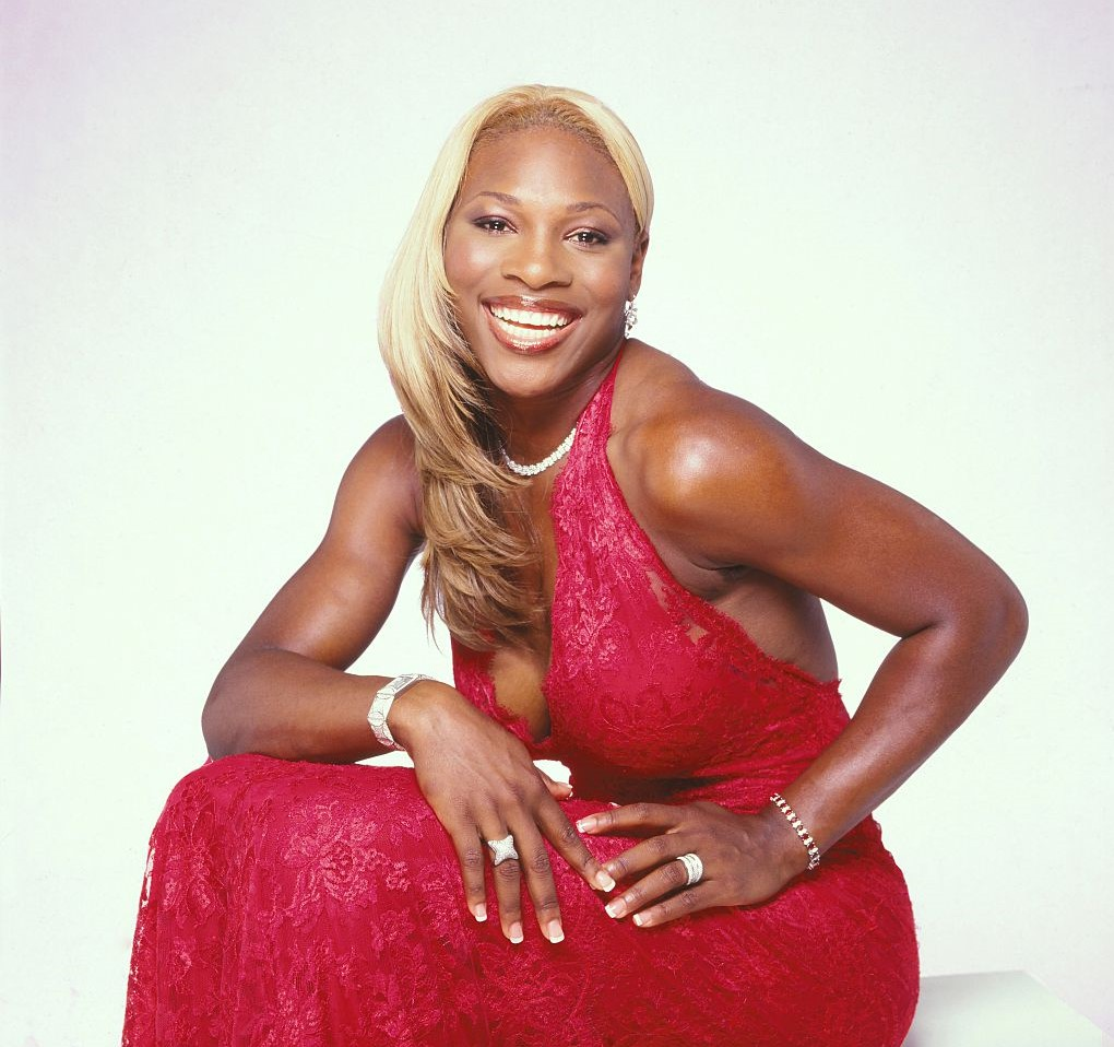 Serena Williams poses in a red violet dress during a photoshoot.