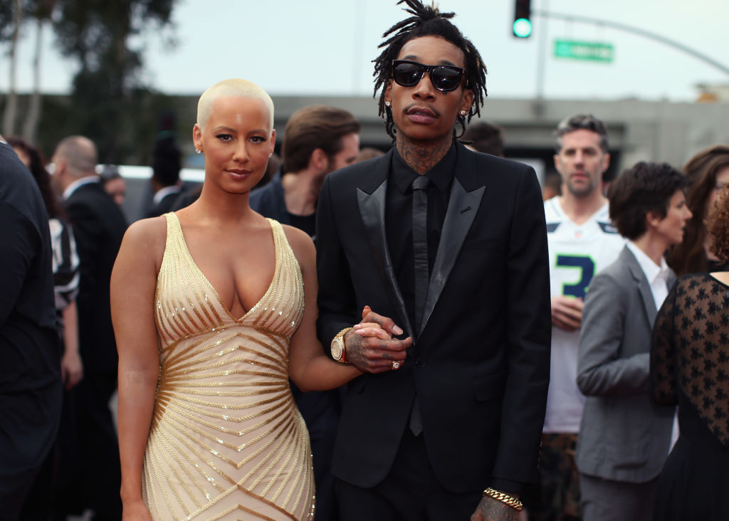 Amber and Wiz hold hands while at an event.