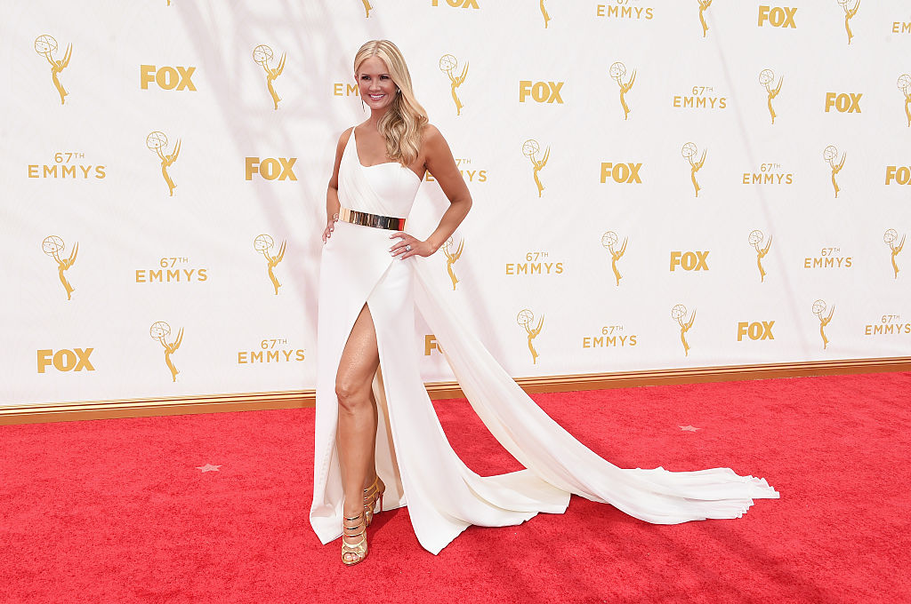 Nancy O'Dell wears a white gown with a trail, slit, and a gold belt.