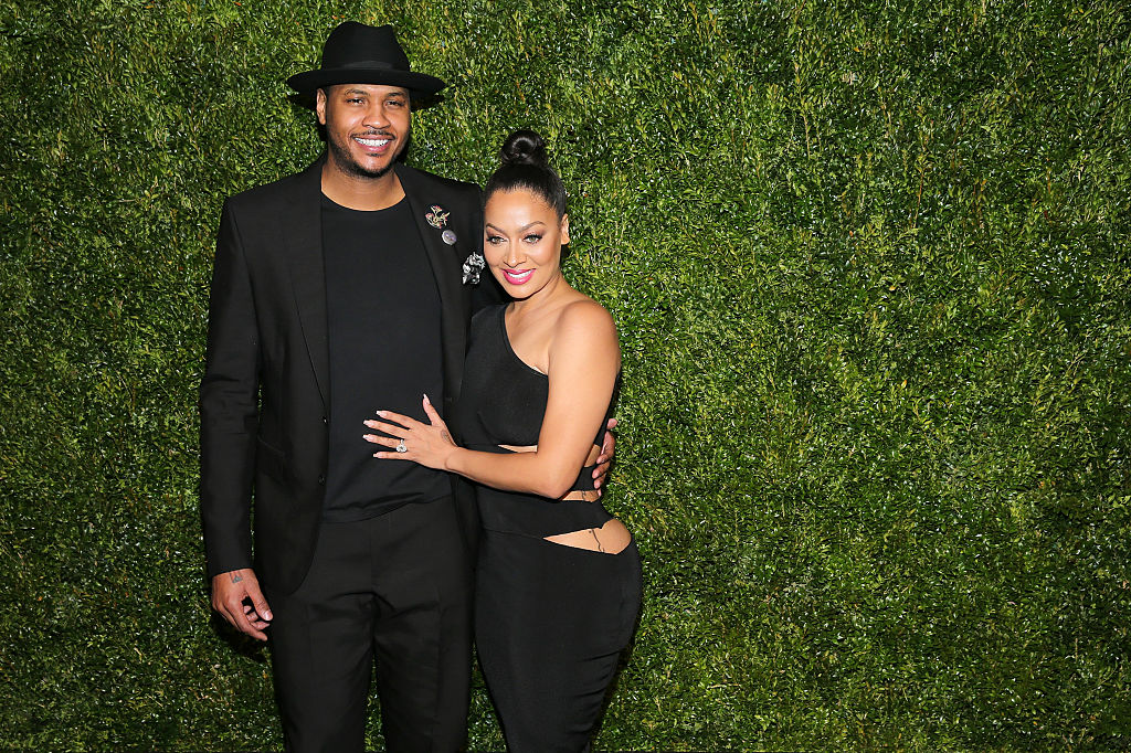 Carmelo and La La pose together in front of a tall hedge.