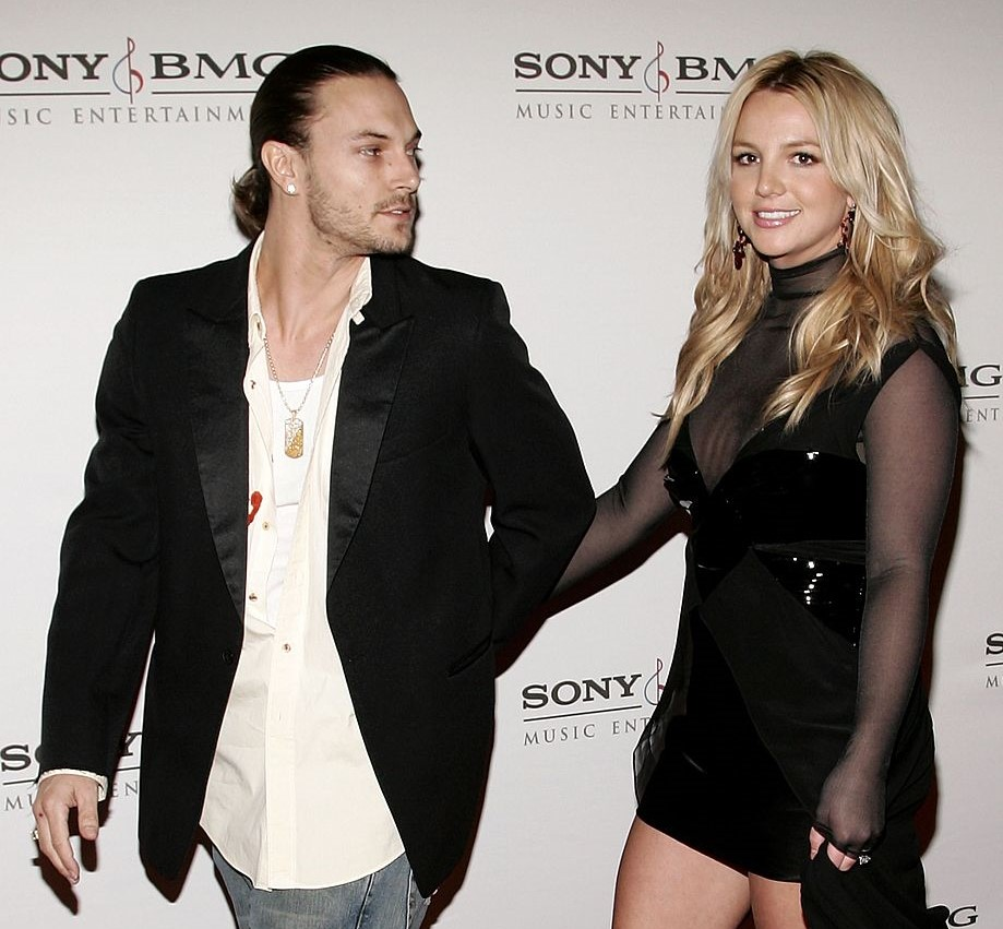 Kevin looks back at Britney as they walk past photographers at an event.