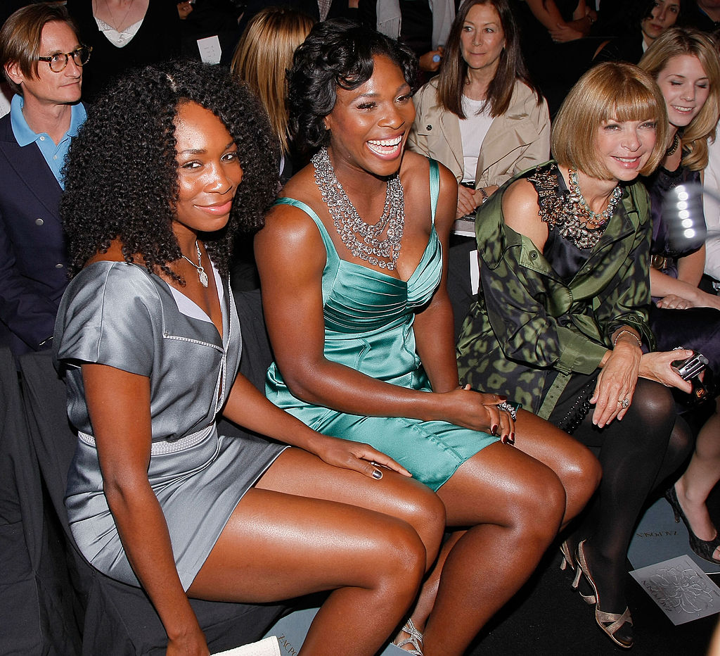 Serena laughs while sitting in the front row at a fashion show.