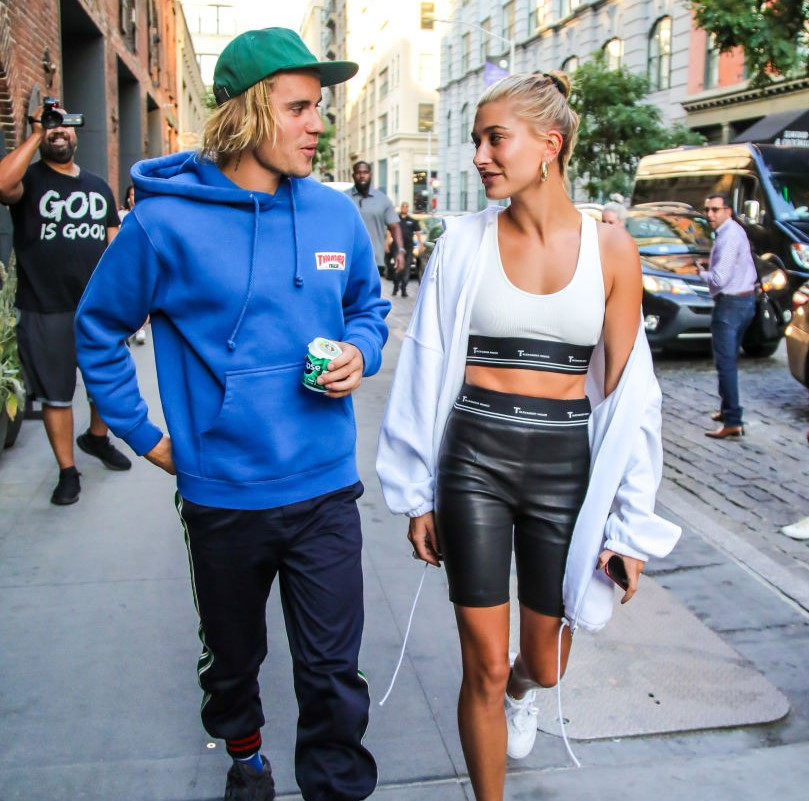 Justin and Hailey look at one another while walking down a street.