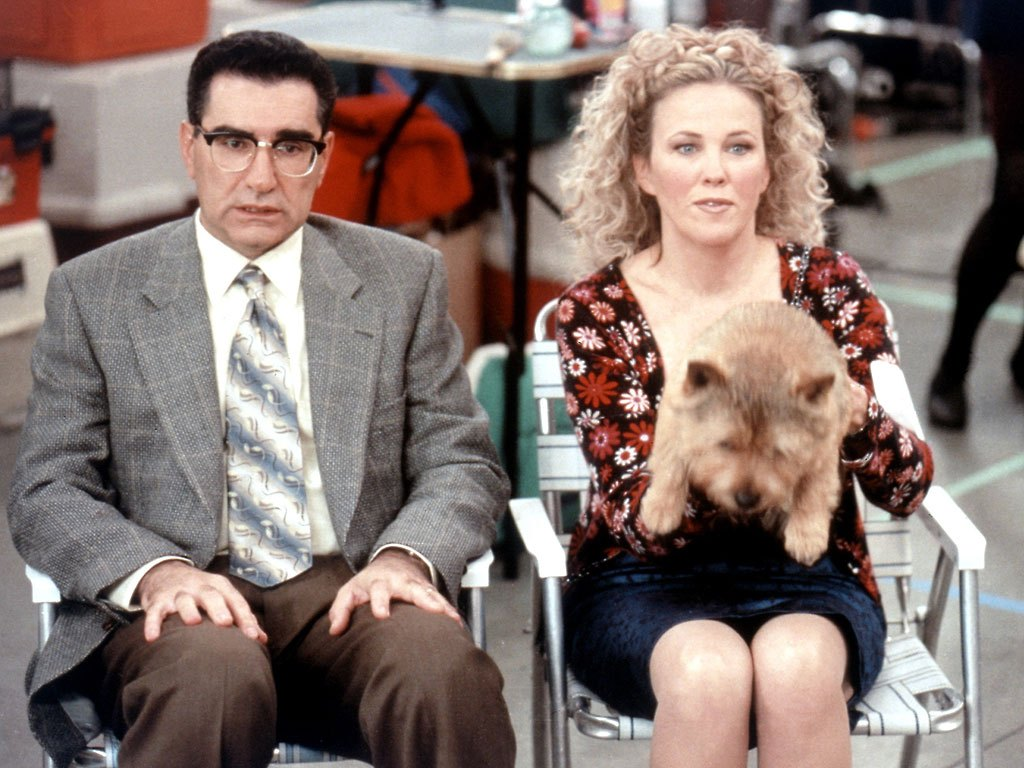 eugene levy and catherine o'hara with a dog on her lap sitting in lawn chairs in best in show