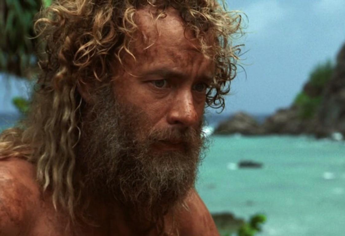 tom hanks on a beach with a beard and long hair in cast away