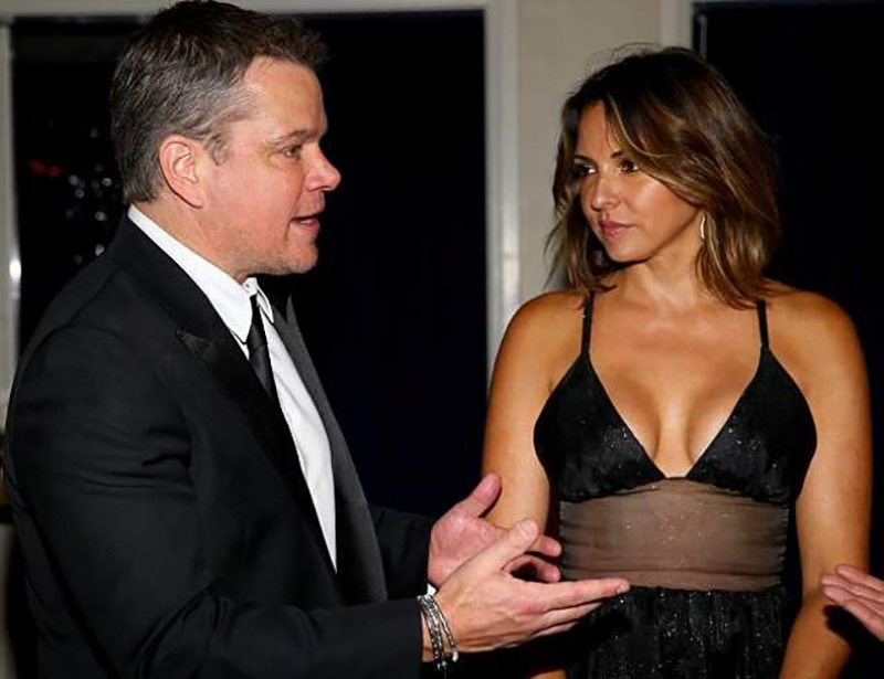 Matt Damon's wife watches him as he talks to someone else.