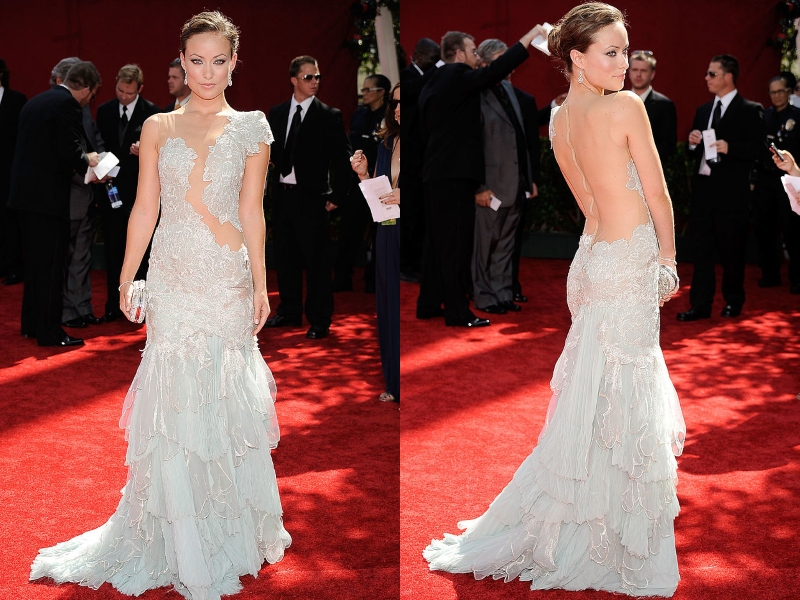 Olivia Wilde wears an off-white gown that gives the illusion of having an open back.