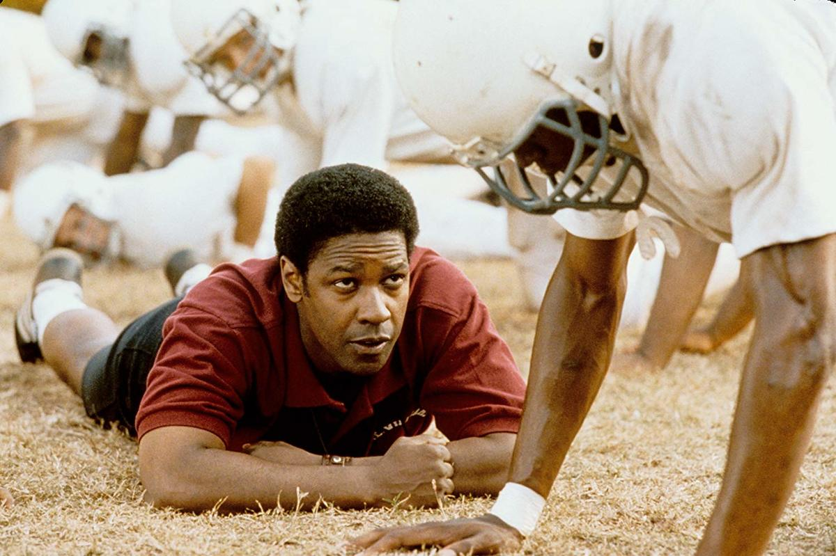 denzel washington laying on a football field with players in remember the titans