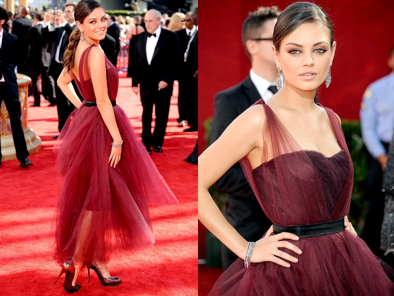 Mila Kunis wears a maroon gown layered in matching tool.