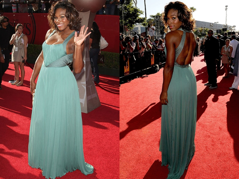 Serena Williams waves to photographers on a red carpet wearing a blue-green gown.
