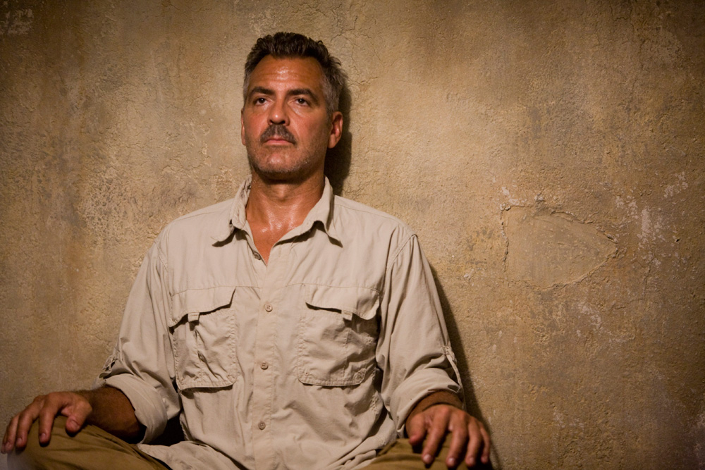 george clooney sitting against a wall in the men who stare at goats