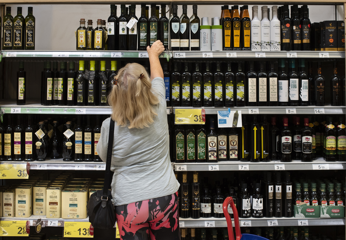 A woman selects a bottle of olive oil from a grocery store shelf.