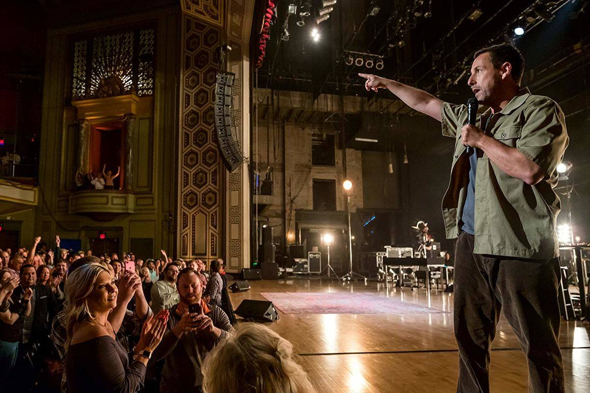 adam sandler performing stand up for a crowd in a theater