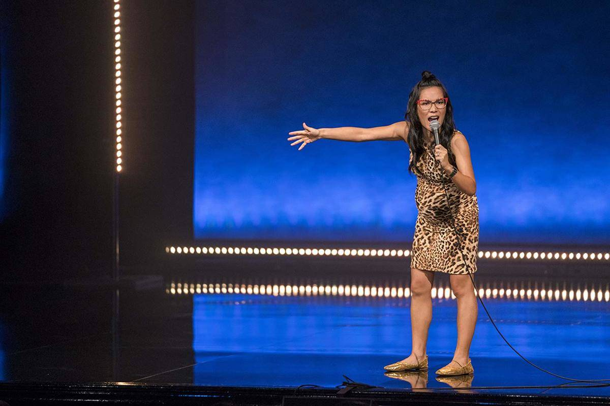 ali wong stretching out her arm and holding a microphone