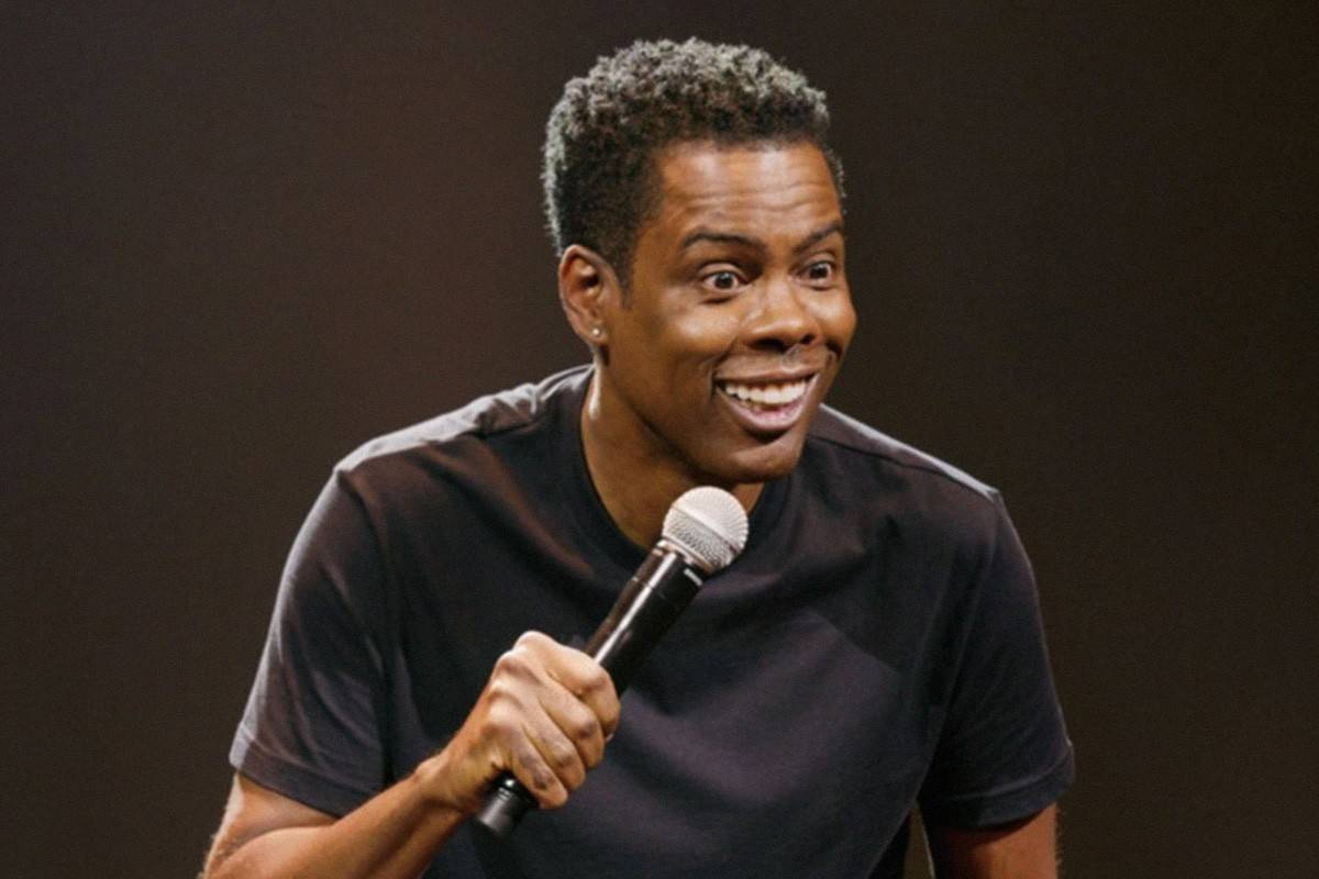 chris rock smiling with a microphone
