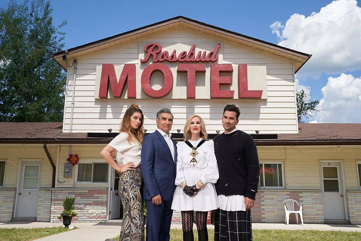 the cast of schitt's creek standing in front of the rosebud motel