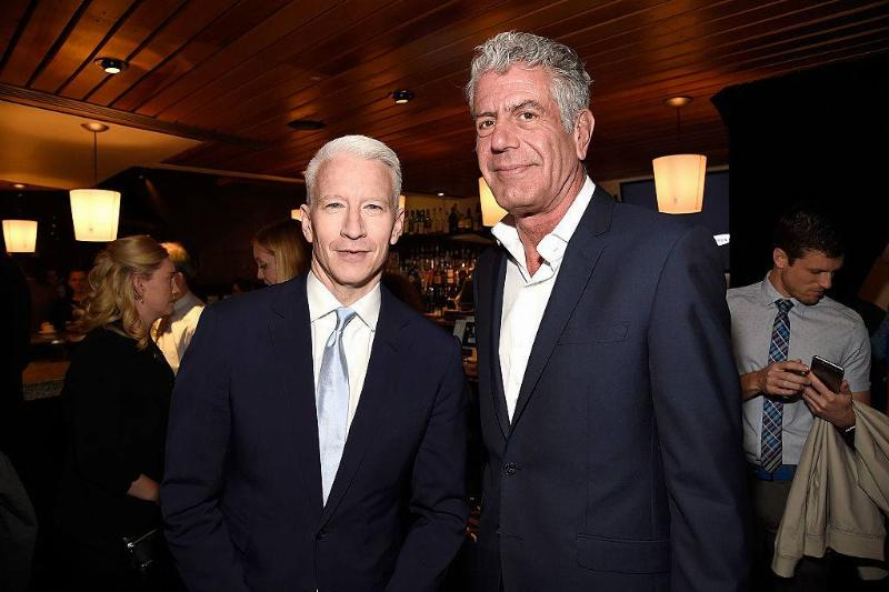anthony bourdain and cooper posing for a photo