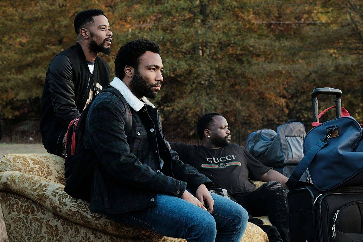 cast of atlanta sitting on a couch outside