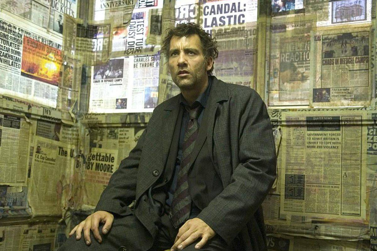 clive owen sitting in a room full of newspapers