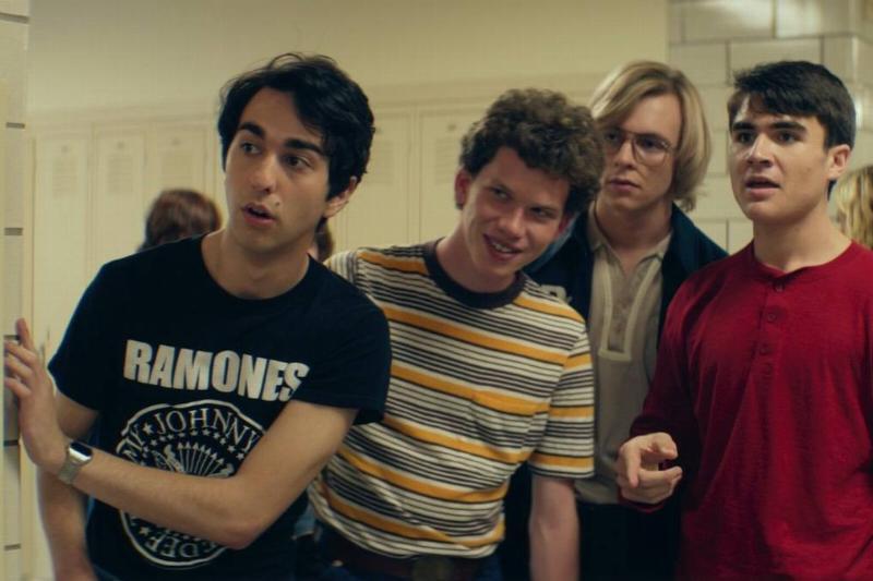 four boys standing near lockers