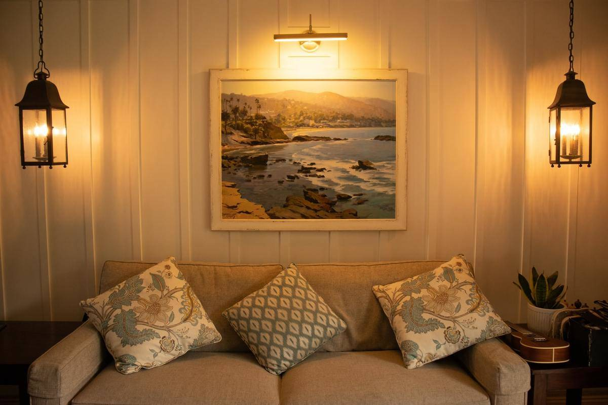 A living room has a beach painting on the wall and couch throw pillows to match.