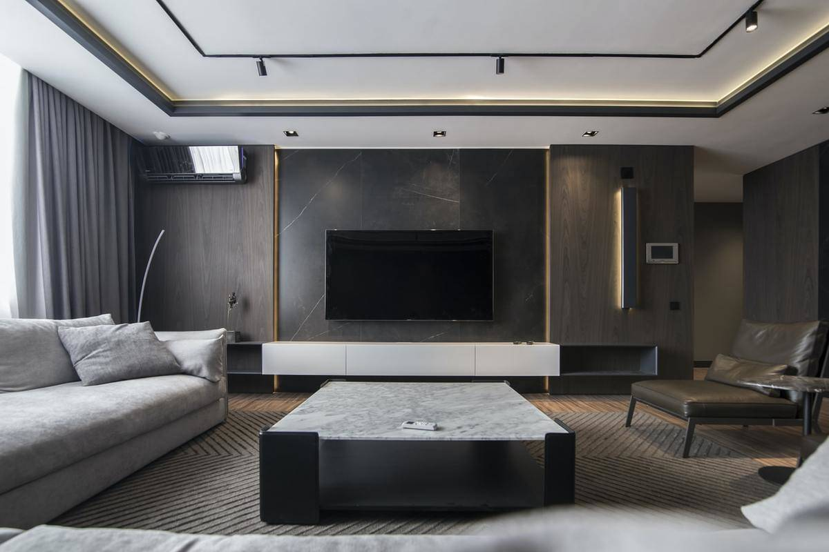 A flat-screen TV hangs on a dark accent wall in a moody living room.
