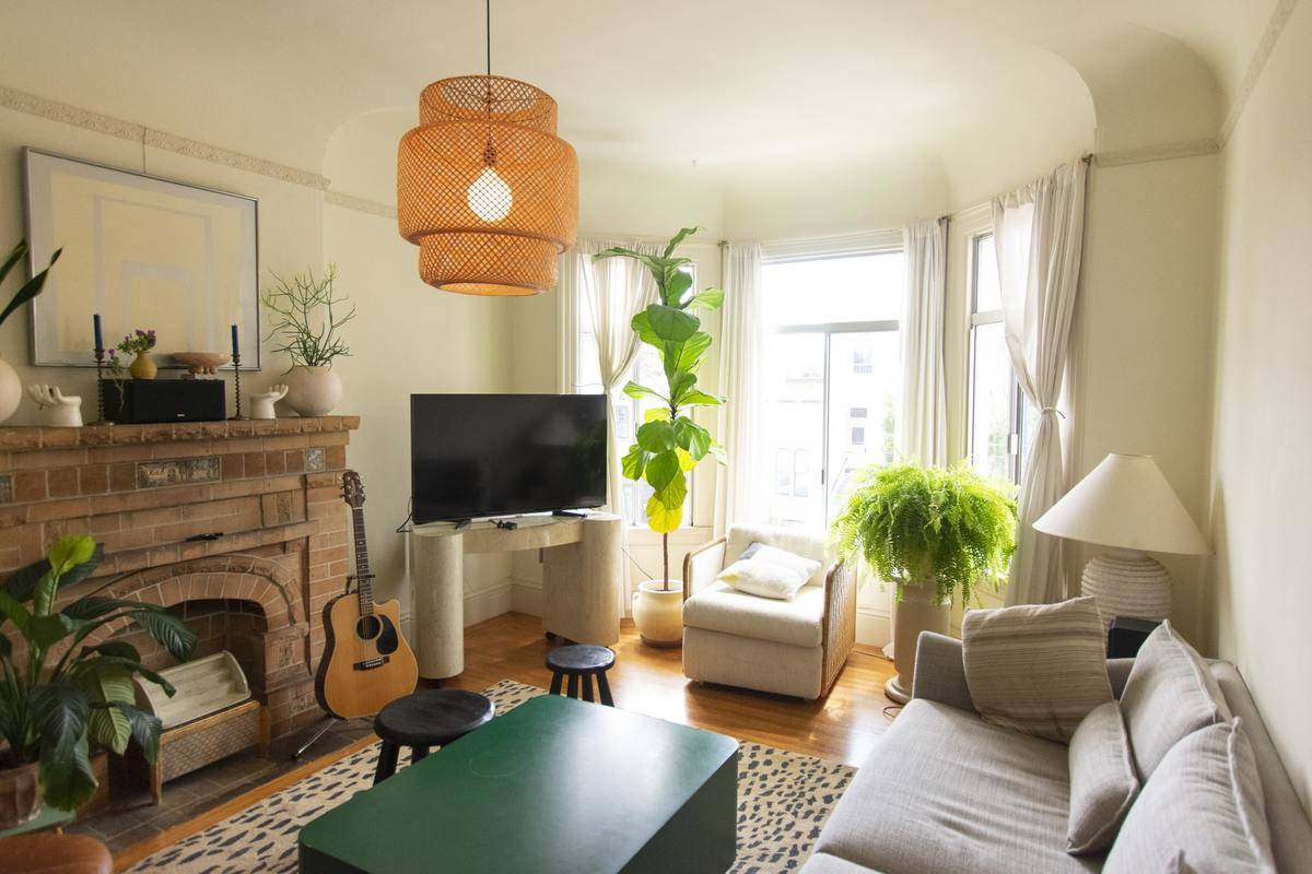A living room has live plants and a brick fireplace.