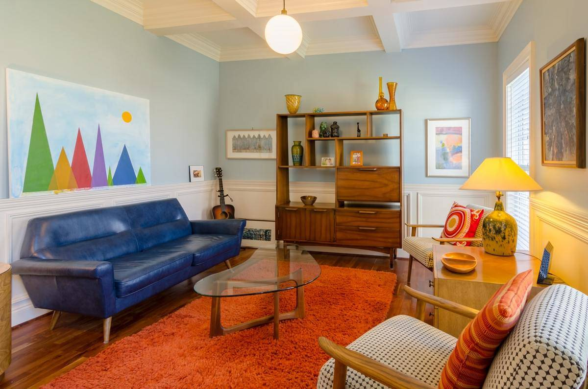 A mid-century modern living room features a blue couch, orange rug, and colorful art.