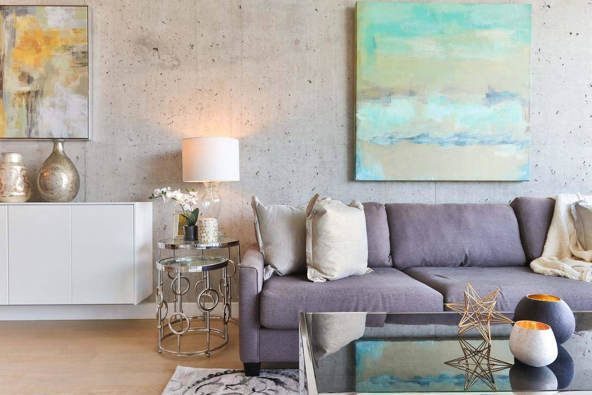 A living room has a decorative silver side table and a purple couch.